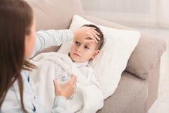 Сестра касаясь лбу ее брата, проверяя температуру стоковые изображения rf