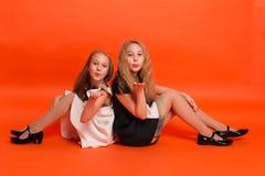 2 сестры в красивых стилизованных платьях на красной предпосылке внутри Стоковое Изображение RF