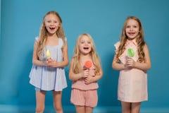 3 сестры девушек едят сладкий леденец на палочке с десертом сладкого шоколада стоковые фото