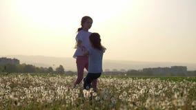 2 сестры держа руки объезжая на glade одуванчиков в парке города outdoors Свобода и беспечальное видеоматериал