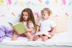 Сестры детей прочитали книгу в кровати Стоковая Фотография