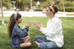 2 сестры играя в парке сидя на траве Стоковое Изображение RF