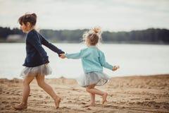 2 сестры играя на береге озера Стоковые Фотографии RF
