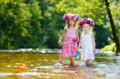 2 сестры играя с бумажными шлюпками рекой Стоковое Изображение