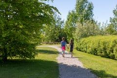 2 сестры идут рука об руку вдоль грязной улицы Стоковые Изображения RF