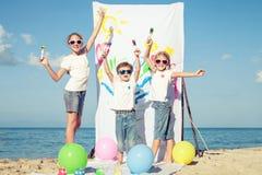 2 сестры и брат играя на пляже на времени дня Стоковая Фотография