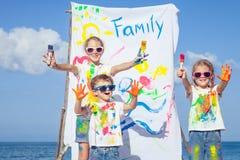 2 сестры и брат играя на пляже на времени дня Стоковые Фото