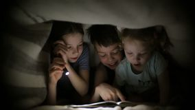2 сестры и брат прочитали книгу под одеялом с электрофонарем в темной комнате на ноче Дети играют видеоматериал