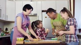 Сестры и родители протягивают толстое тесто над варить таблицу сток-видео