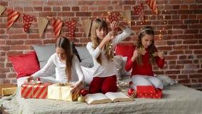 3 сестры одели в пижамах сидя на украшенной кровати для рождества, девушках xmas тройни раскрывая настоящие моменты акции видеоматериалы