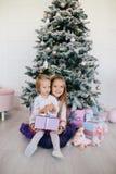 Сестры дома с рождественской елкой и настоящими моментами Портрет счастливых девушек детей с подарочными коробками и украшениями  Стоковые Фото