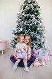 2 сестры дома с рождественской елкой и настоящими моментами Счастливые девушки детей с подарочными коробками и украшениями рождес Стоковое фото RF