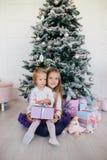2 сестры дома с рождественской елкой и настоящими моментами Счастливые девушки детей с подарочными коробками и украшениями рождес Стоковые Фотографии RF