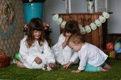 Сестры отпрысков в nightgowns играя с кроликом стоковое фото rf
