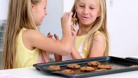 Сестры подавая одину другого свежие печенья акции видеоматериалы