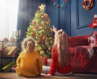 Сестры приближают к рождественской елке Стоковые Фотографии RF