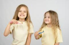 2 сестры с зубными щетками Стоковые Изображения
