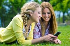 2 сестры с smartphone на парке стоковые изображения