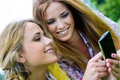 2 сестры с smartphone на парке стоковое фото rf