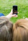 2 сестры с smartphone на парке стоковое изображение rf