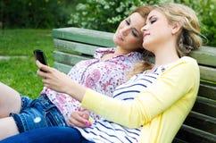 2 сестры с smartphone на парке Стоковая Фотография