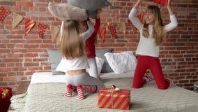 Сестры троен в пижамах аранжировали бой подушками Спальня украшена гирляндами рождества и xmas акции видеоматериалы