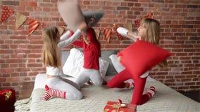 Сестры троен одетые в пижамах xmas имеют бой подушками на кровати, которая украшена для рождества, веселой видеоматериал