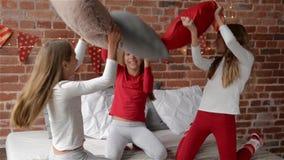 Сестры троен одетые в пижамах xmas имеют бой подушками на кровати, которая украшена для рождества, веселой акции видеоматериалы