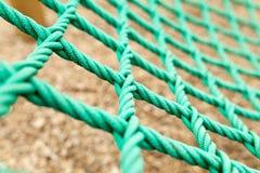 Сетка веревочки с расплывчатой предпосылкой Зеленая сетка веревочки в спортивной площадке Нет совершенно новой сетки веревочки но стоковое фото