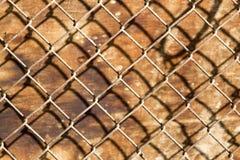 Сетка металла на деревянной предпосылке Стоковые Изображения RF