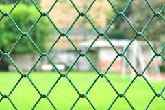 Сетка металла с предпосылкой футбольного поля нерезкости стоковая фотография