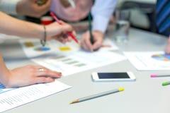 Сеть команды дела - таблица офиса с диаграммами и руками людей Стоковые Фото