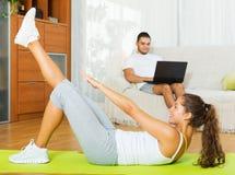 Сеть просматривать Гая пока девушка делая exercices Стоковые Фотографии RF