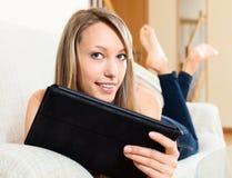 Сеть просматривать молодой женщины с таблеткой Стоковая Фотография