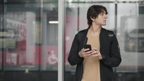 Сеть человека занимаясь серфингом и смотря вокруг на железнодорожном вокзале акции видеоматериалы