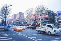 СЕУЛ, ЮЖНАЯ КОРЕЯ - 29-ое декабря 2014: Оживленная улица с автомобилями и различными магазинами в Ittaewon Стоковое Фото