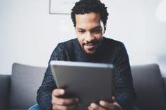 Селективный фокус Взгляд крупного плана привлекательных бородатых африканских новостей чтения человека на цифровой таблетке пока  Стоковые Изображения RF