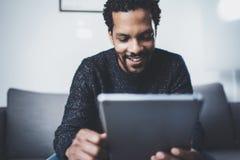 Селективный фокус Взгляд крупного плана привлекательных молодых африканских новостей чтения человека на цифровой таблетке пока си Стоковое Изображение RF
