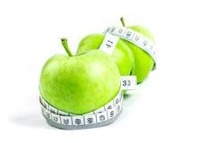 Селективный фокус зеленого яблока с измеряя лентой на задней части белизны Стоковая Фотография RF