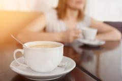 Селективный фокус на чашке с ароматичным кофе Запачканная предпосылка с кофейной чашкой девушки выпивая Стоковые Изображения RF