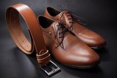 Селективный фокус пояса и ботинка людей кожаного на деревянном столе Стоковые Изображения