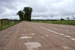 Сельская дорога гравия с лужицами после дождя Стоковая Фотография