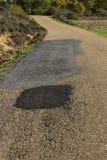 Сельская дорога с рытвинами Стоковая Фотография