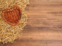 Сельская предпосылка eco корзина Лоз-работы от с в формы сердца с соломой на предпосылке старых деревянных планок Стоковые Фотографии RF