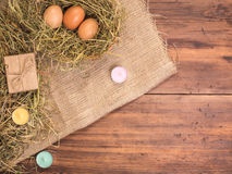 Сельская предпосылка eco при коричневые яичка цыпленка, покрашенная свечи, подарочная коробка и солома на предпосылке старых дере Стоковые Изображения