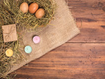 Сельская предпосылка eco при коричневые яичка цыпленка, покрашенная свечи, подарочная коробка и солома на предпосылке старых дере Стоковое Фото
