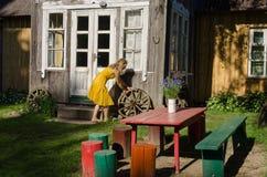Сельские двор и девушка дома свертывают старое колесо экипажа Стоковая Фотография RF