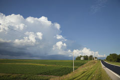 Сельские дорога и поля midwest под большими облаками Стоковые Изображения RF