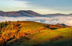 Сельские поля над облаками в горах на восходе солнца Стоковые Фотографии RF