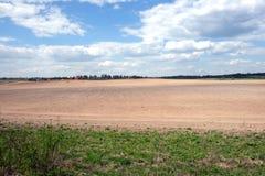 Сельский ландшафт с вспаханным полем и деревней далеко Стоковое Изображение